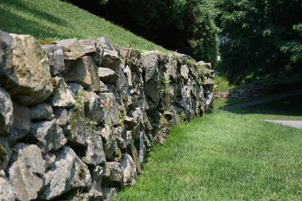 Large rock retaining wall custom installation
